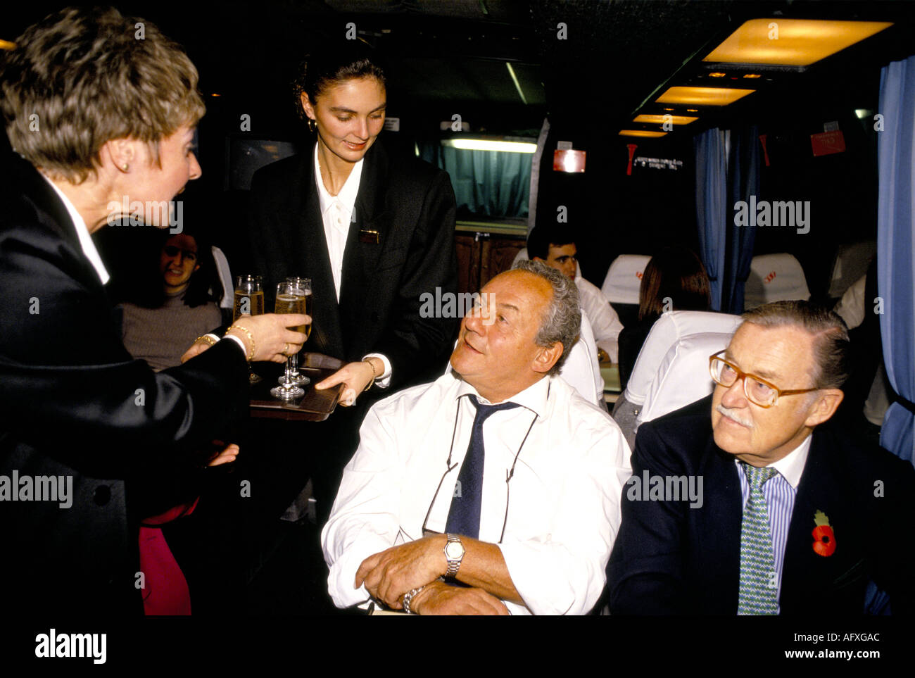 British restaurateur John Gold white shirt TV broadcaster Alan Wicker being served with champagne executive coach Circa 1985 - Stock Image
