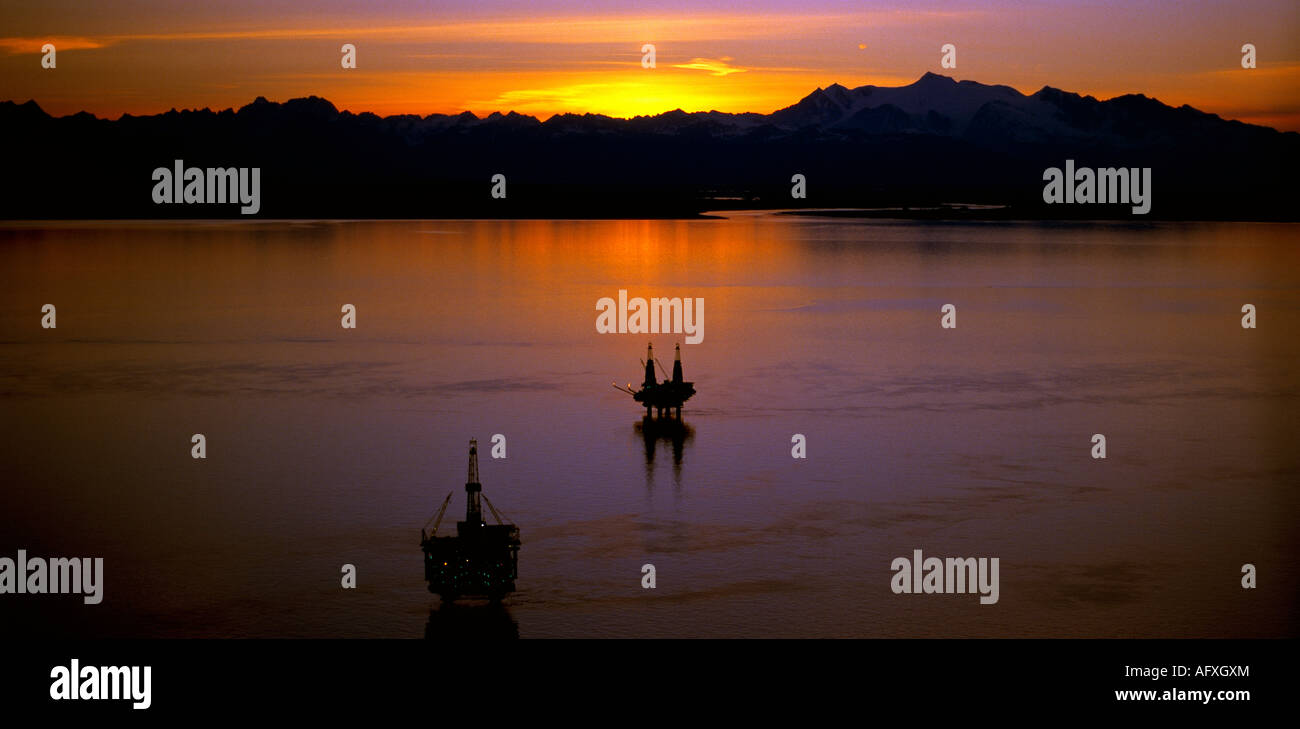 An evening aerial view of the offshore oil exploration in the Cook Inlet of Alaska with the Tordrillo Mountains. - Stock Image