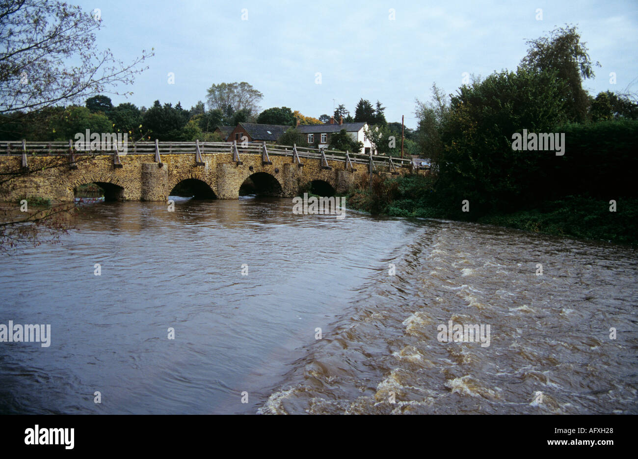 TILFORD SURREY England  UK November The River Wey in flood flowing under the old bridge - Stock Image