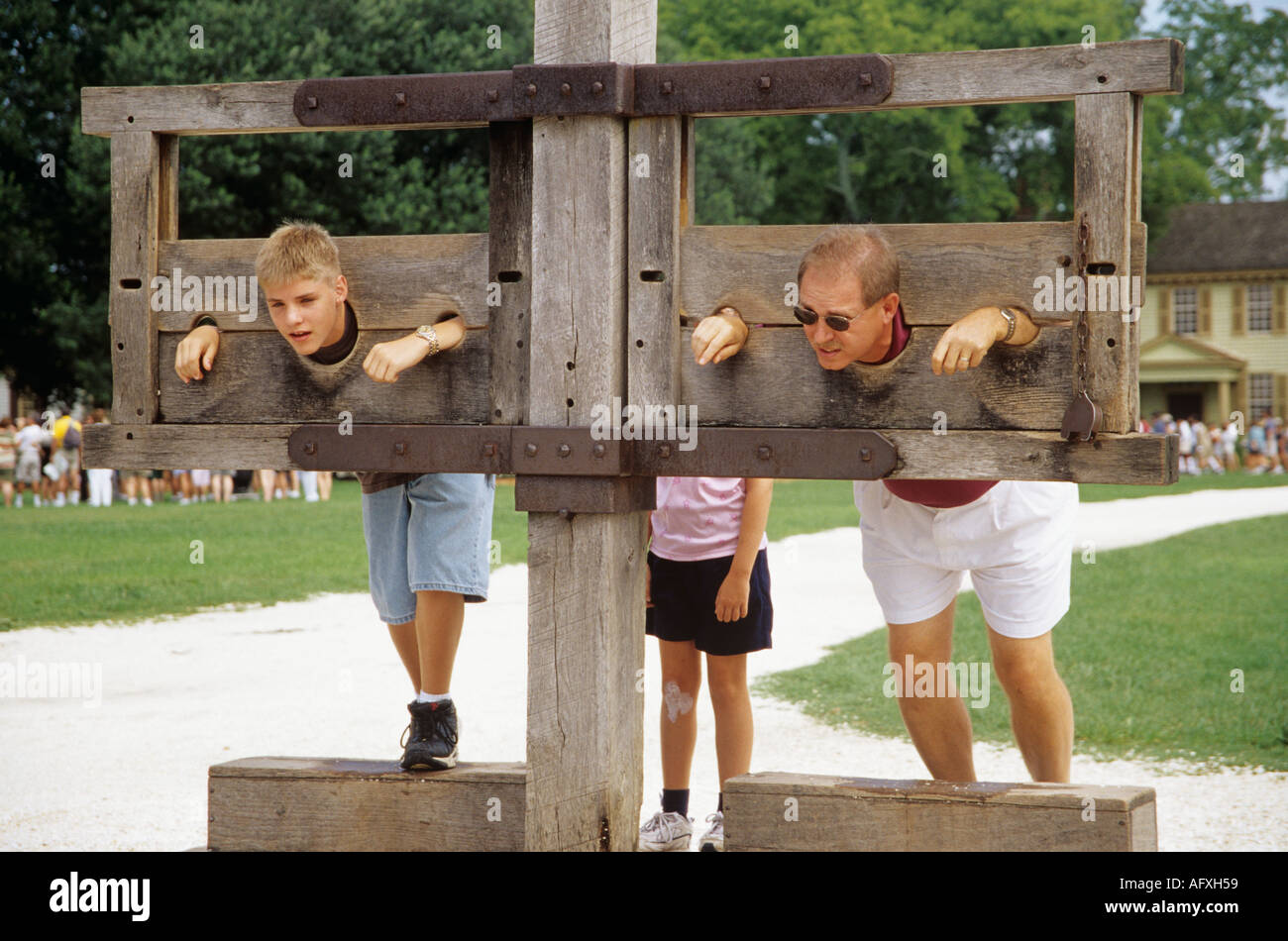COLONIAL WILLIAMSBURG VIRGINIA USA August Man and his son in the stocks outside the Courthouse - Stock Image