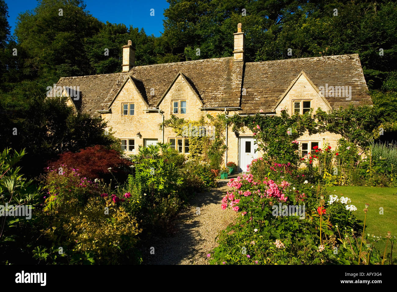 Ancient Cottages Traditional English Cottage Gardens With Flowers In Summer Sunshine Blue Sky At Bibury Cotswolds UK GB