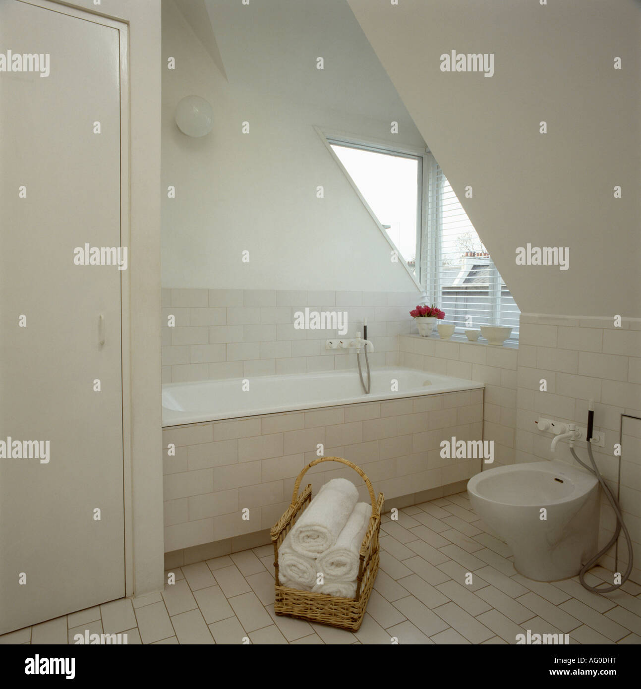 White Towels In Basket On Floor Of Modern White Attic Bathroom With Stock Photo Alamy