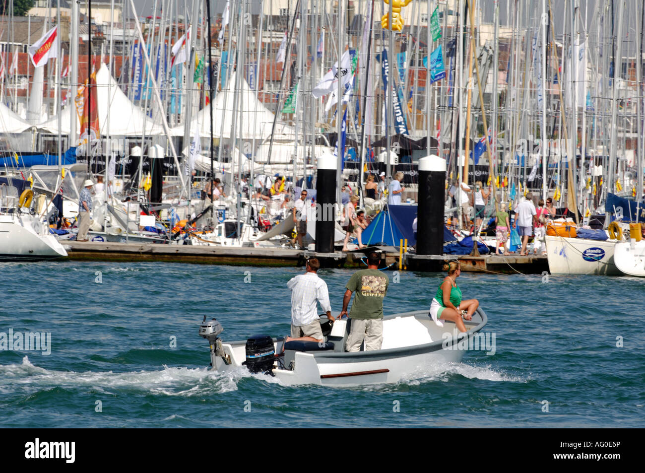 two young men and a young woman in a boat launch on the river medina at cowes during cowes week on the isle of wight Stock Photo