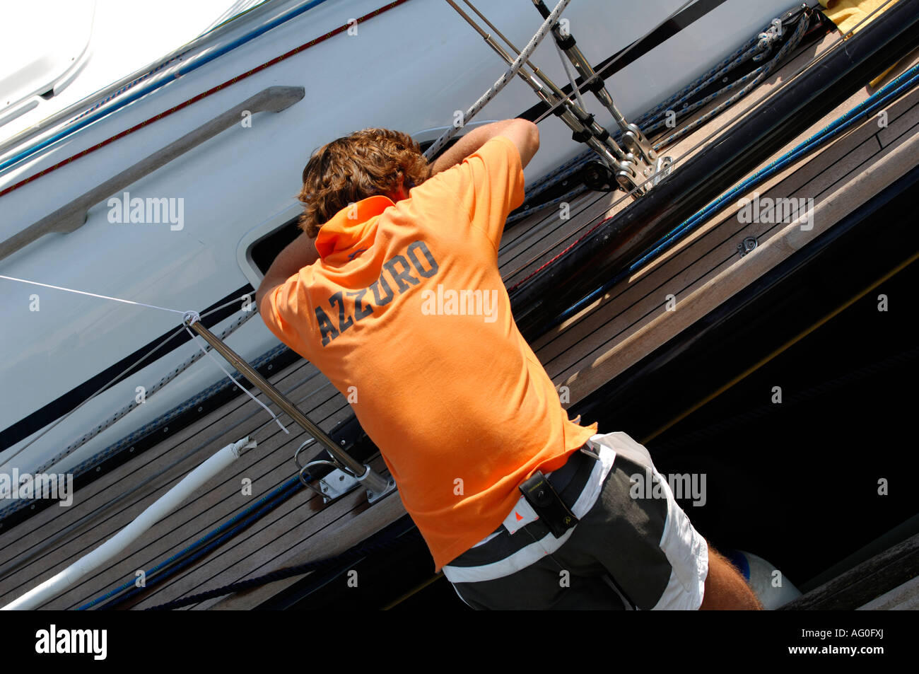 crew member during cowes week resting on side of yacht after long days racing in the solent isle of wight - Stock Image