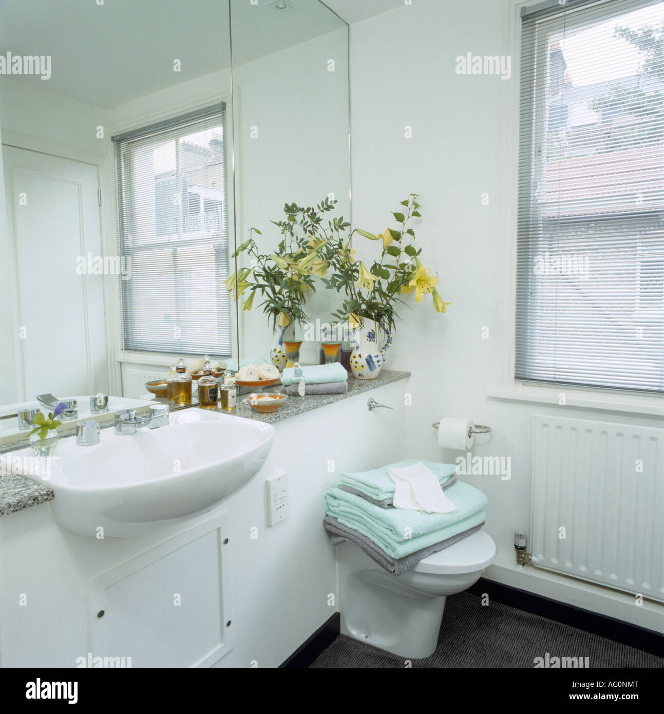 Mirrored Wall Above Basin Built Into Vanity Unit In White Bathroom With  Turquoise Towels On Toilet