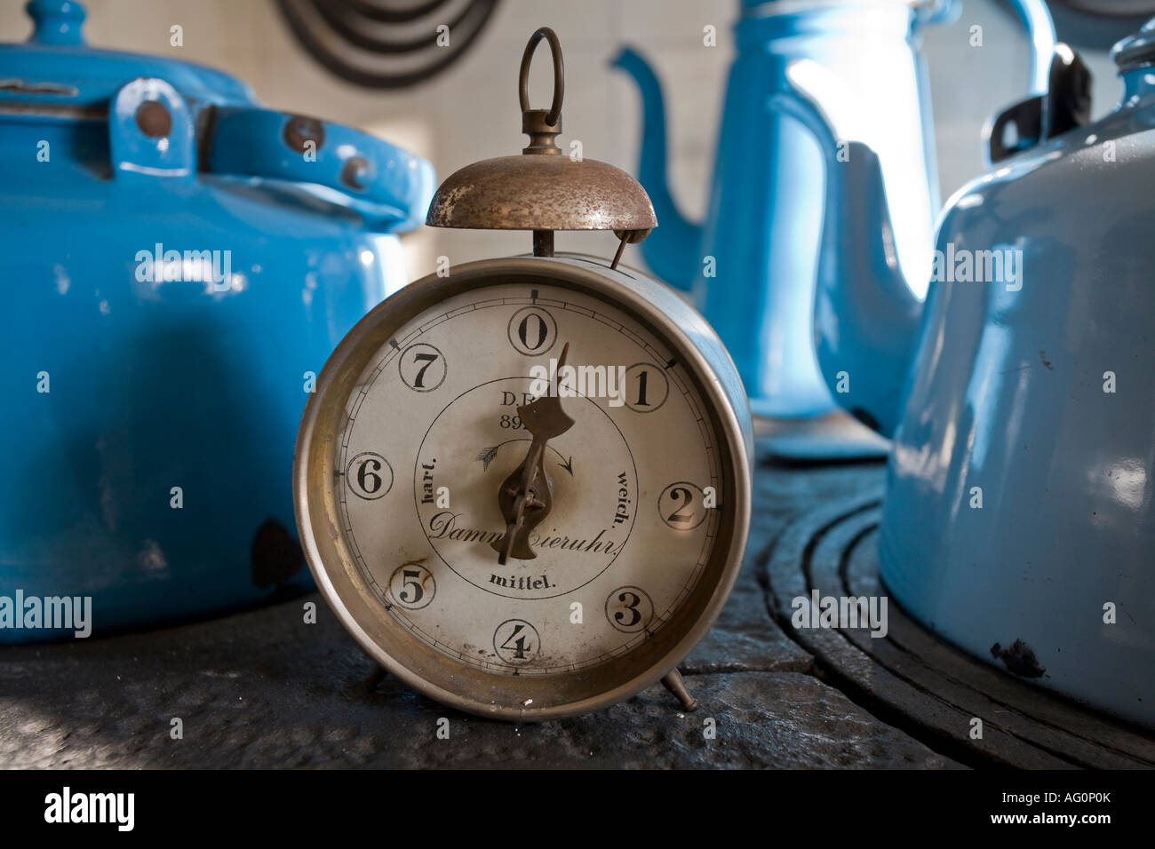 Time for Tea An old antique kitchen timer with a bell on top on a coal stove surrounded by blue kettles Juelsberg - Stock Image