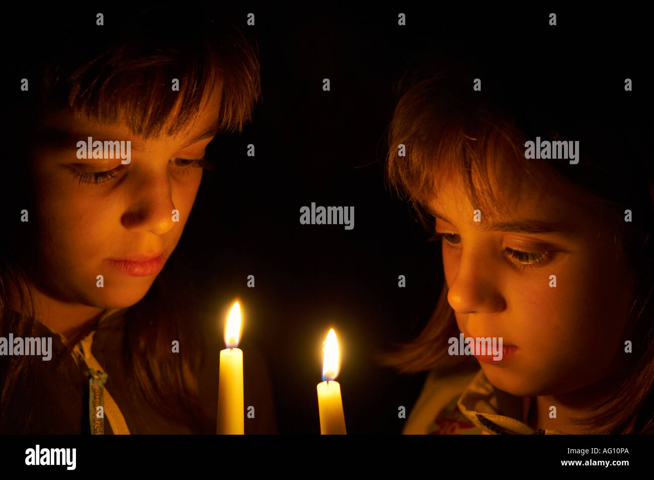 Two pre teen sisters in Brownie uniforms holding lit candles. - Stock Image
