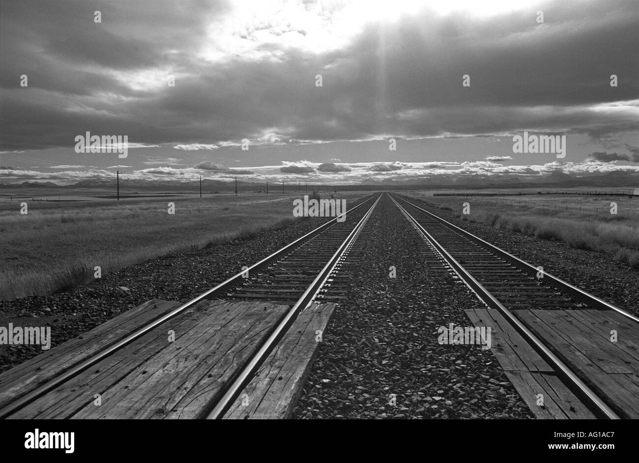 Railroad tracks disappear into the sunset in northern Montana, USA - Stock Image