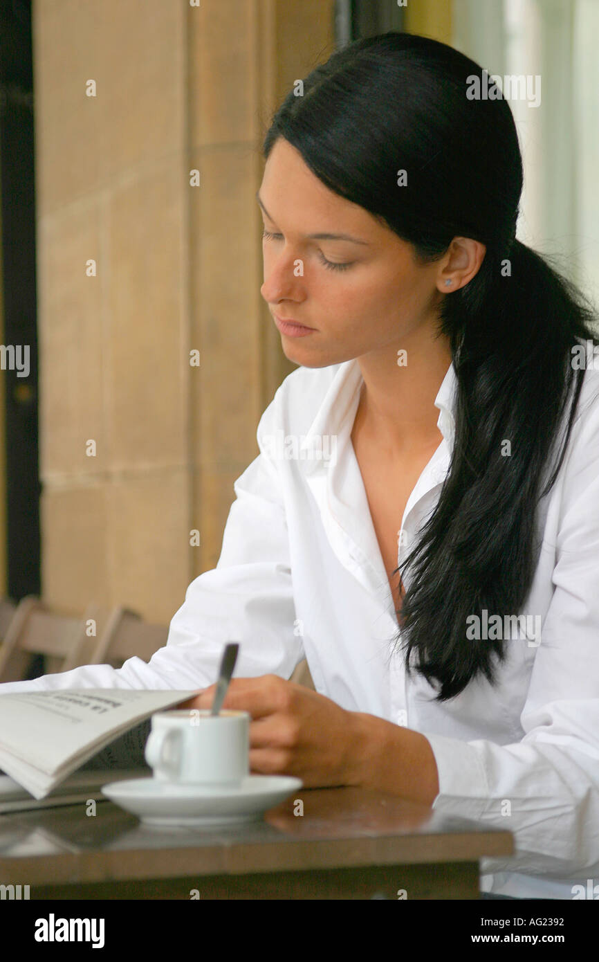 young black haired woman with ponytail reading newspaper at a stock