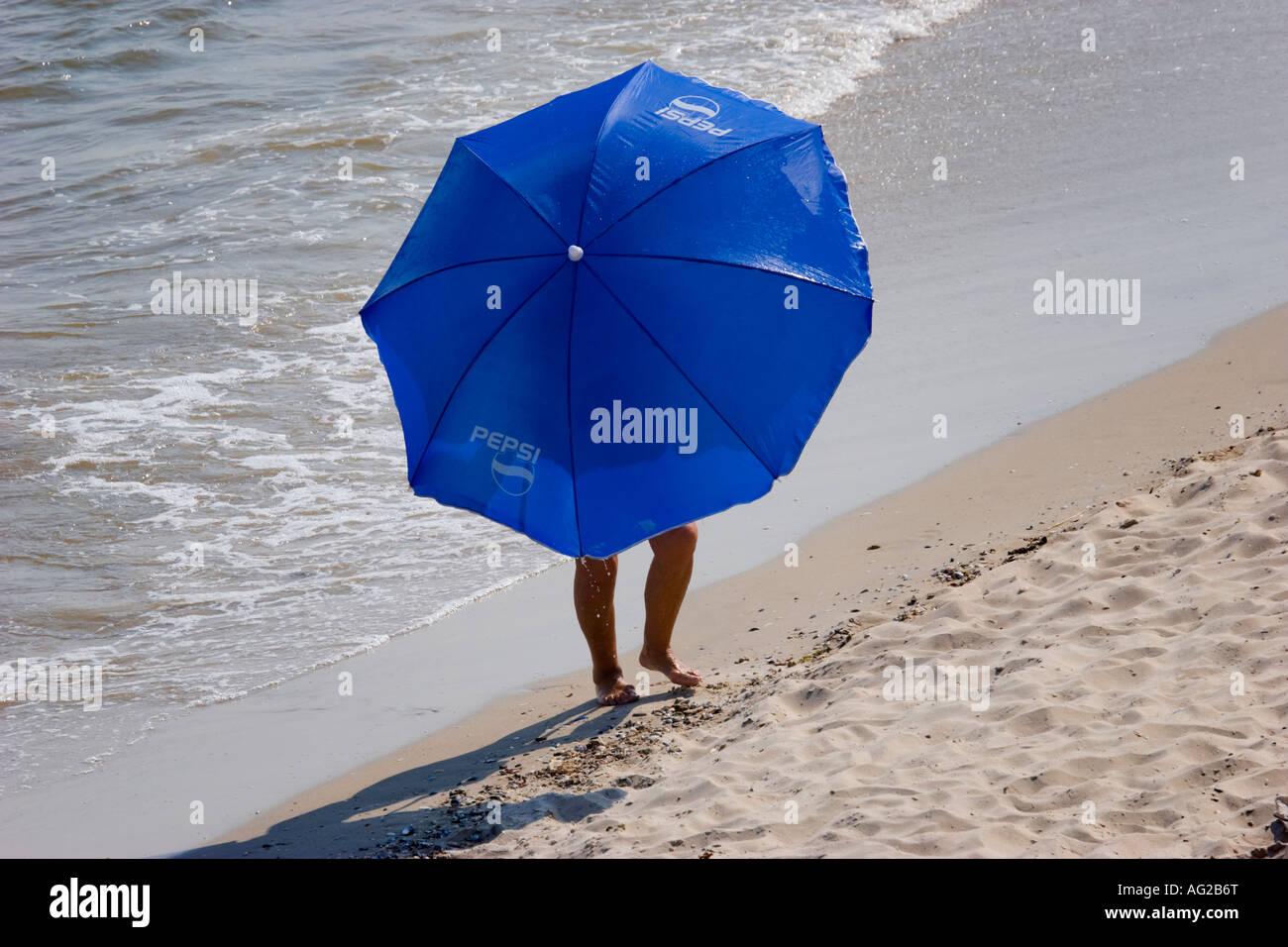 A sun umbrella seems to be walking at the Black Sea beach of Lebedivka / Ukraine - Stock Image