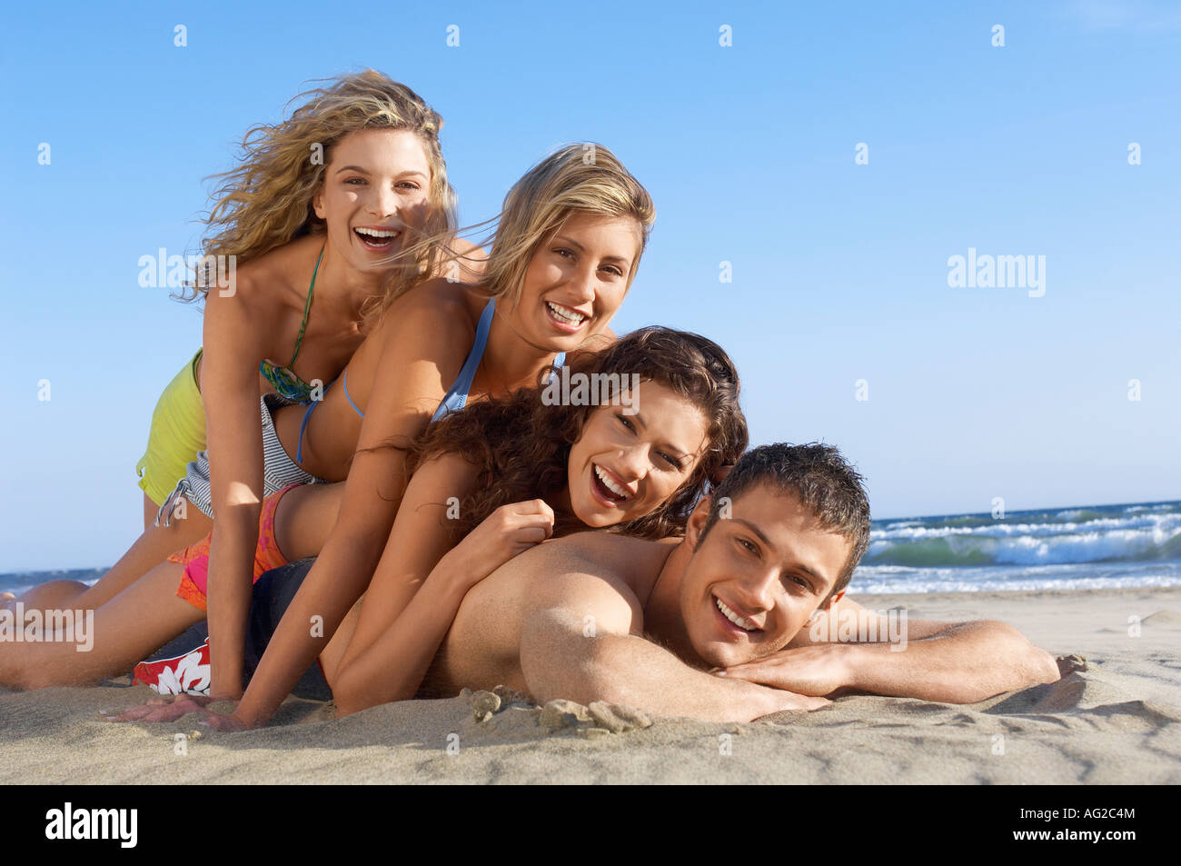 Three young women lying on man on beach, portrait, ground view - Stock Image