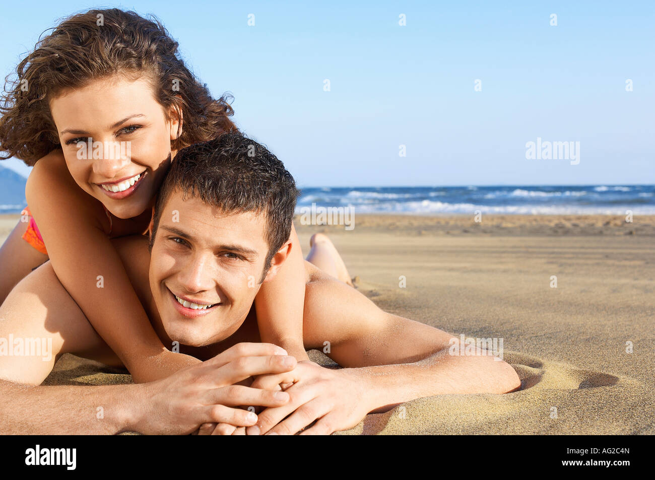 Young woman lying on back of man on beach, portrait, ground view - Stock Image