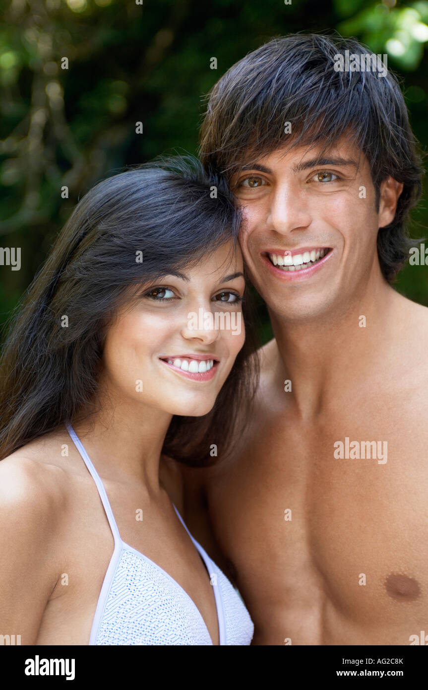 Young couple in swimwear in forest, portrait - Stock Image