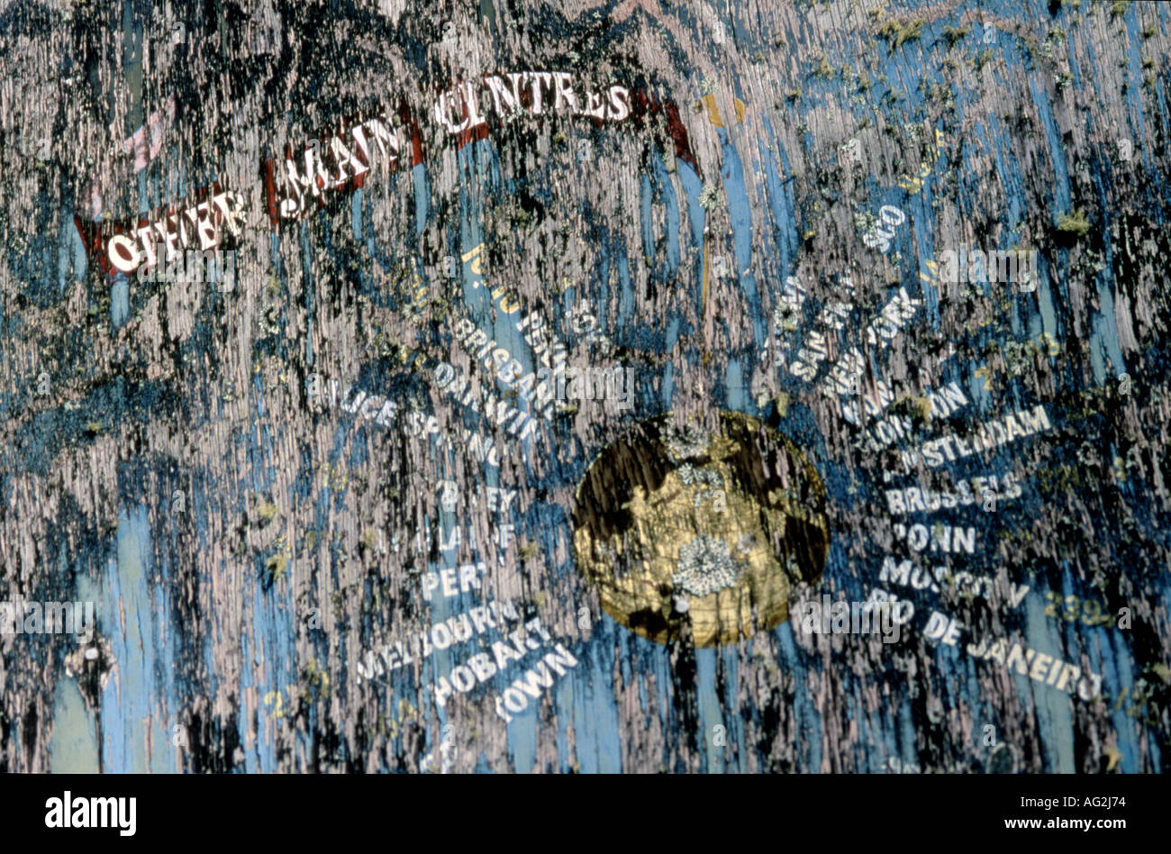 Old weathered sign with globe and famous city names Haast New Zealand - Stock Image