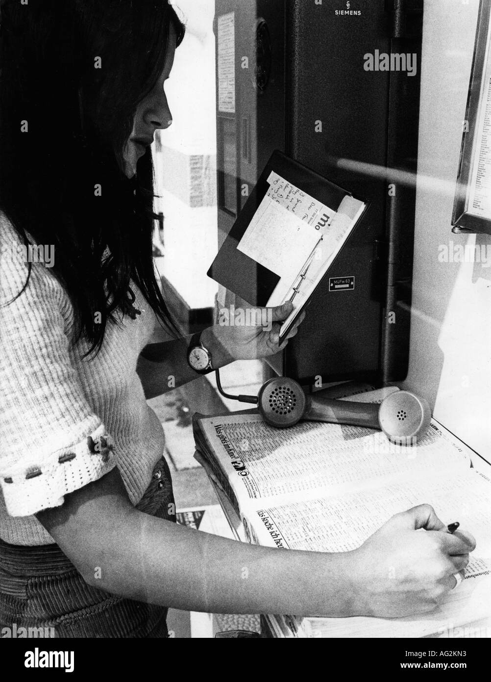 mail/post, telephone, telephone kiosk, young woman searching for a number in a telephone book, Munich, 1971, Additional-Rights-Clearances-NA - Stock Image