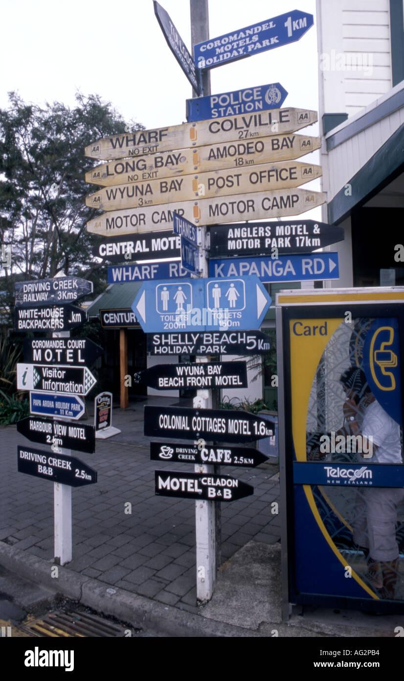 Heavily laden signpost Coromandel Township Coromandel Peninsula New Zealand - Stock Image