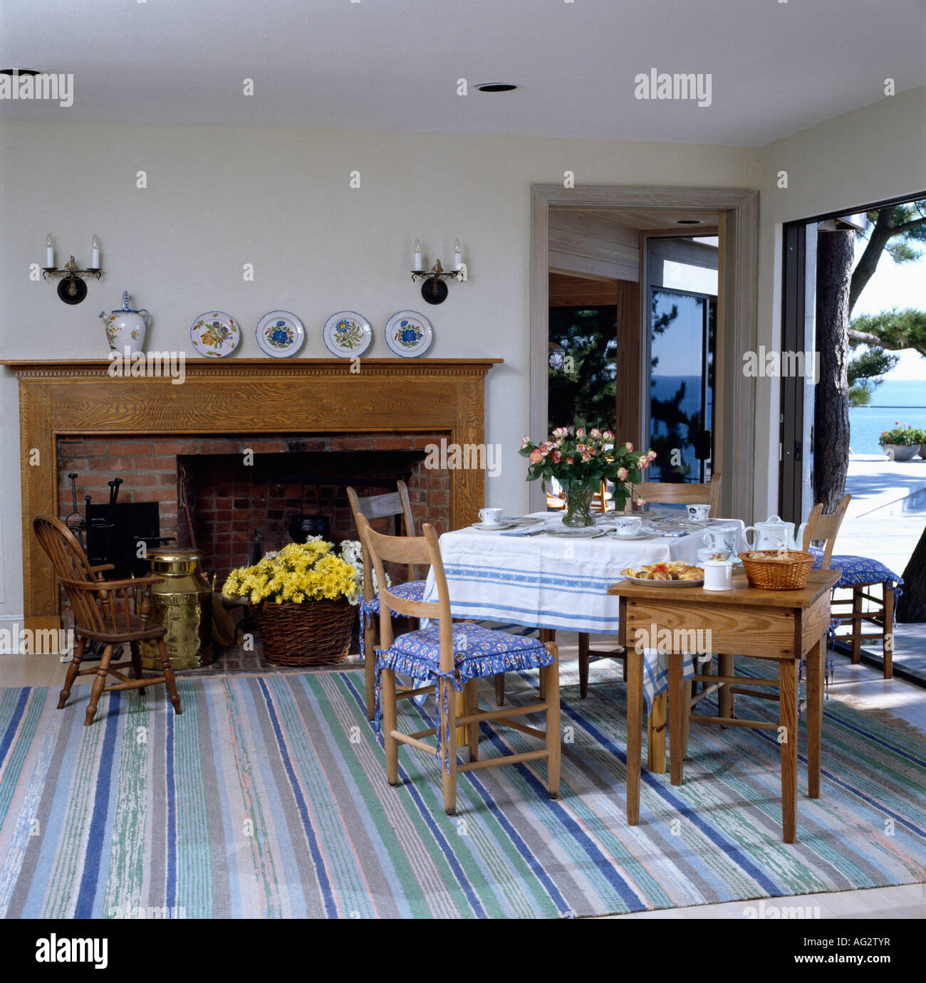 Seaside Dining Room With Wooden Fireplace And Pastel Blue Striped Carpet  And View Of The Ocean Through Glass Doors