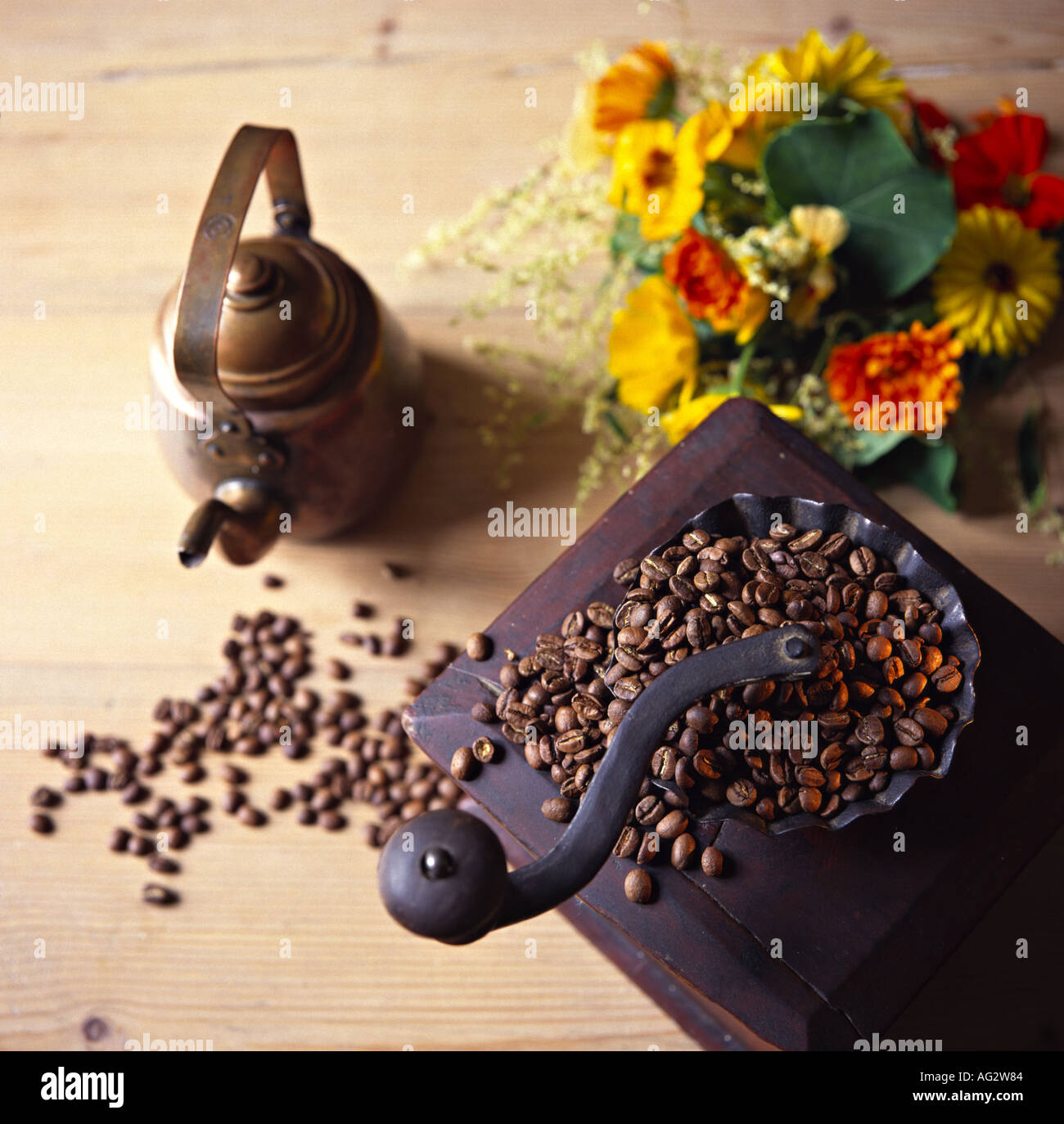 old coffee mill grinder coffee pot made of copper and a coloured flowers - Stock Image