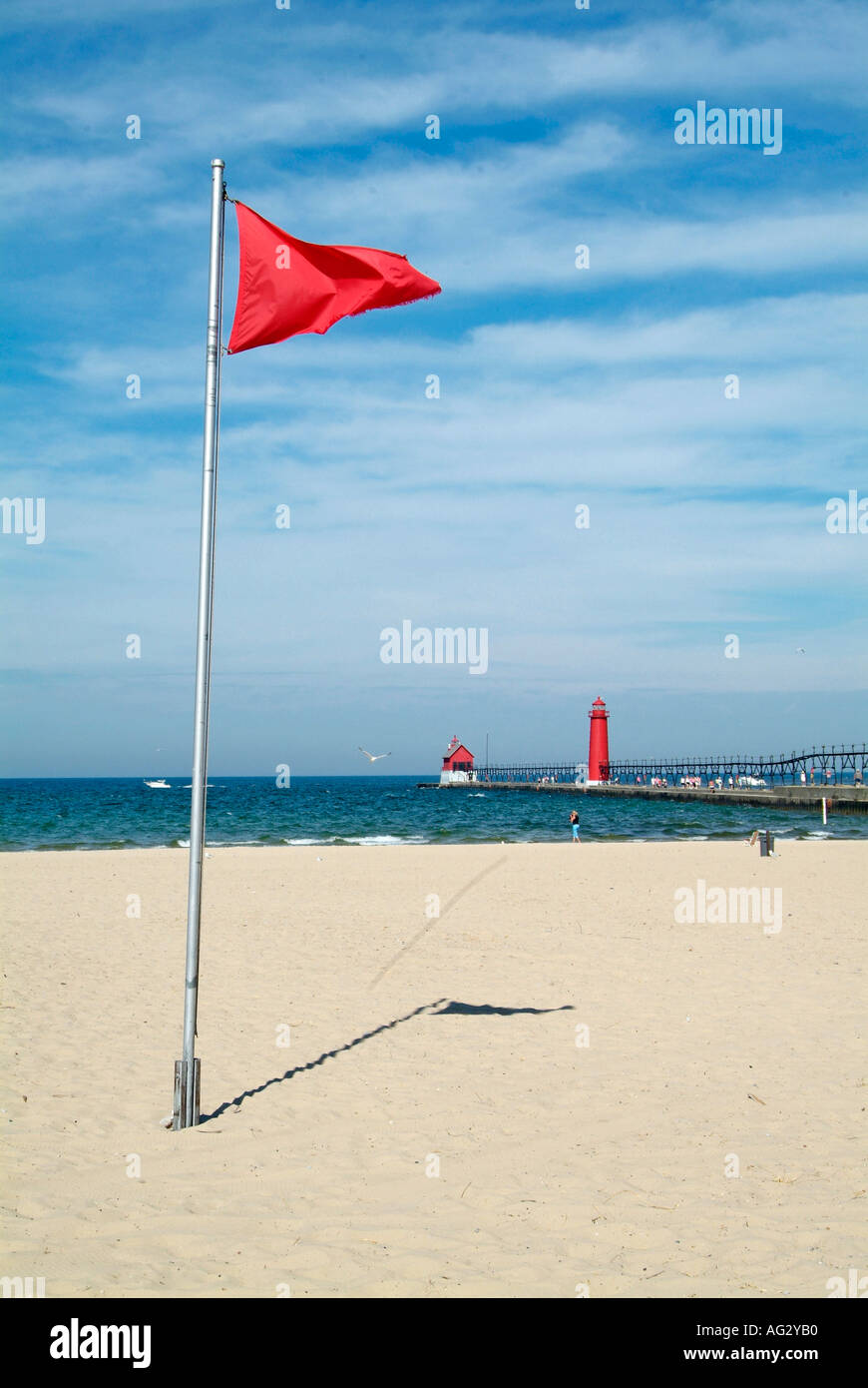 Red flag on Grand Haven State Park Beach warns swimmers of polluted water and swimming is prohibited - Stock Image