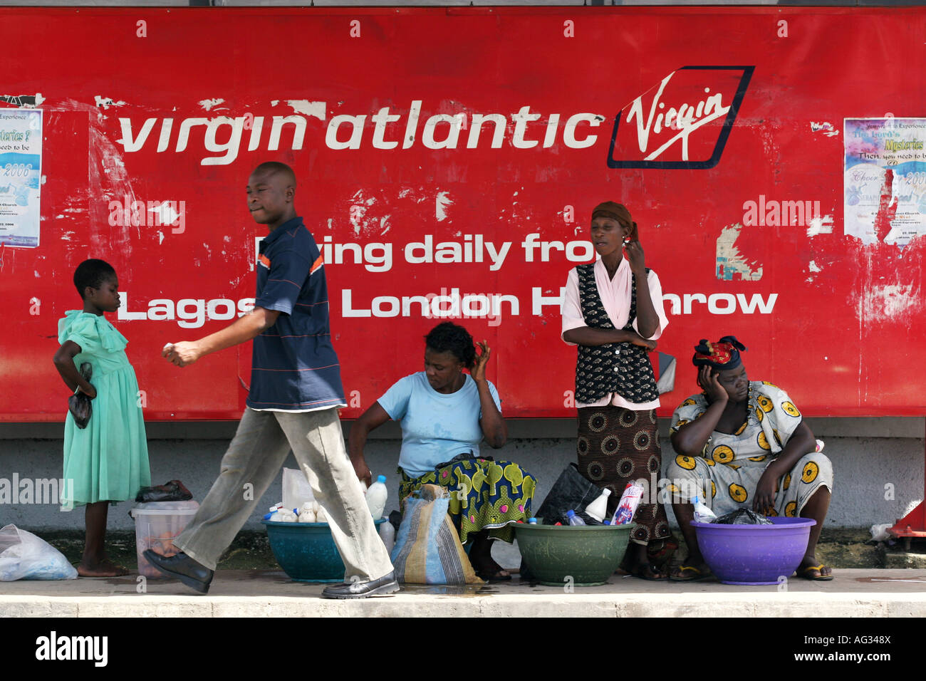A man walks past women selling goods in front of a Virgin Airlines poster Lagos, Nigeria - Stock Image