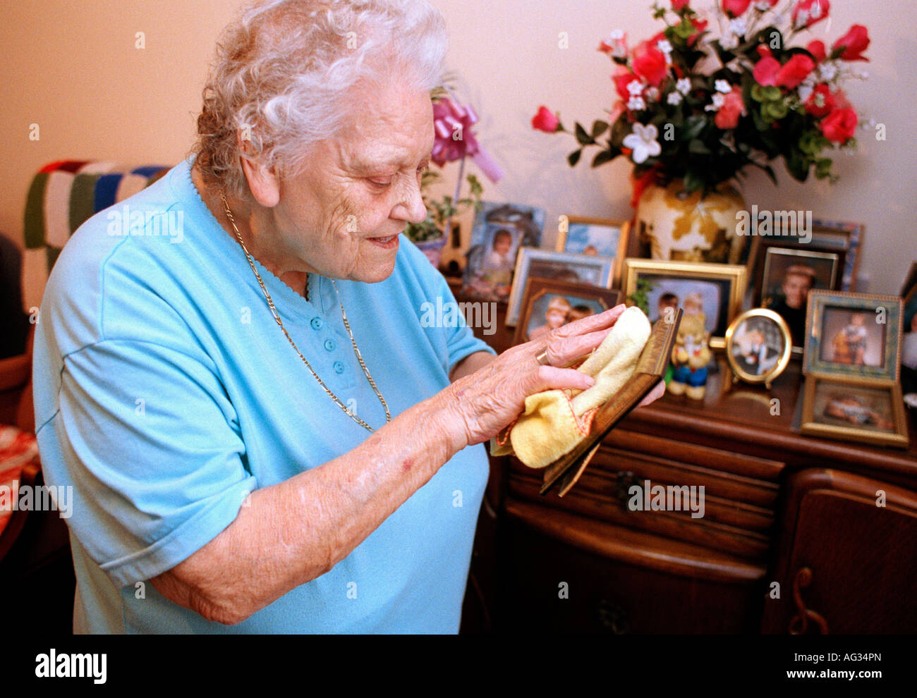 An elderly lady polishes her family photographs in her bedroom at a sheltered housing home in England - Stock Image