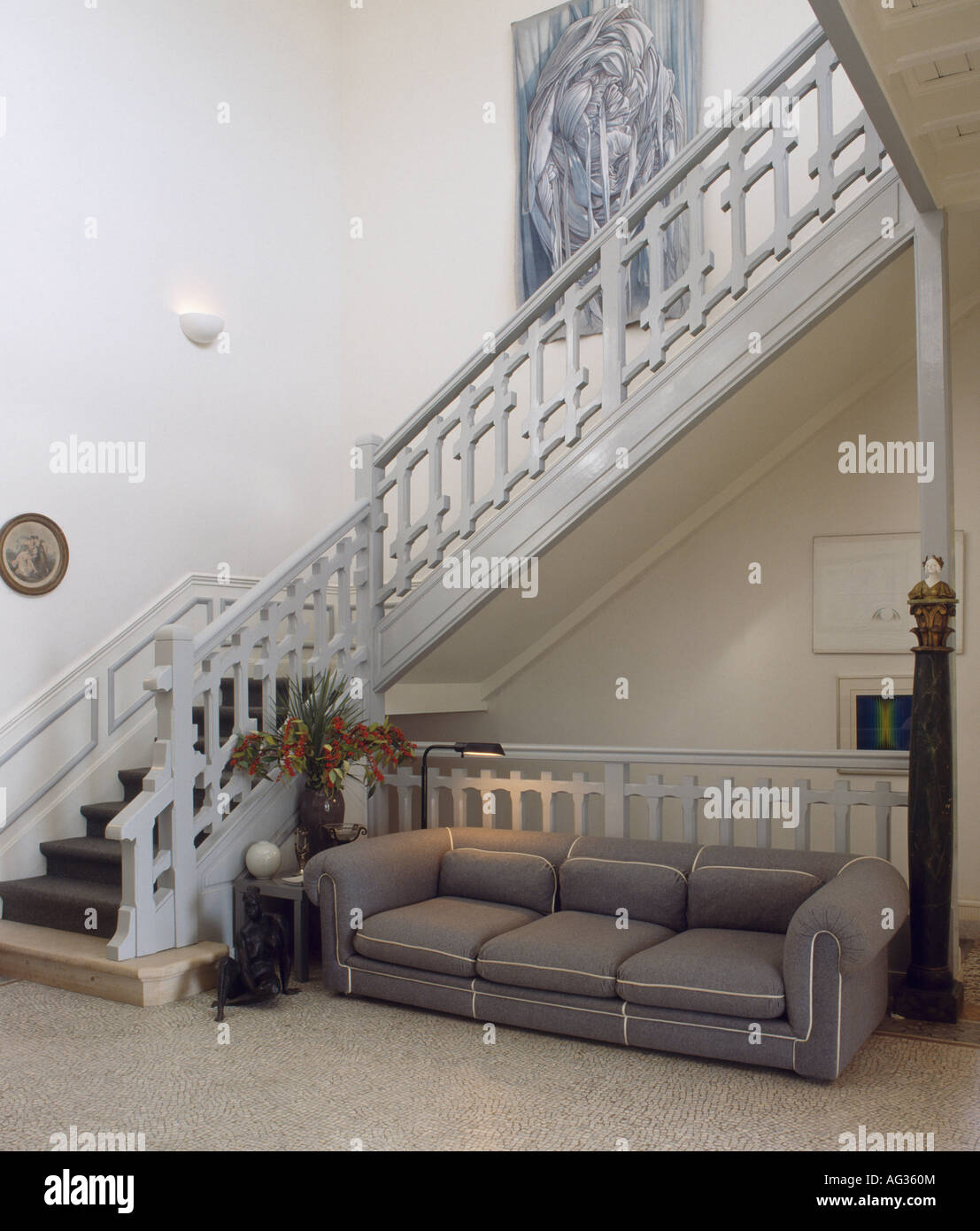Large Grey Sofa Below Traditional White Staircase In Monochromatic