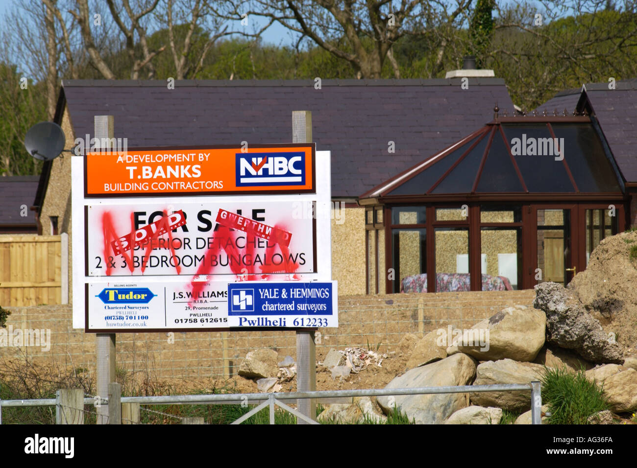 Defaced for sale signs at a new housing development in a campaign against high property prices at Llanystumdwy North Wales UK - Stock Image