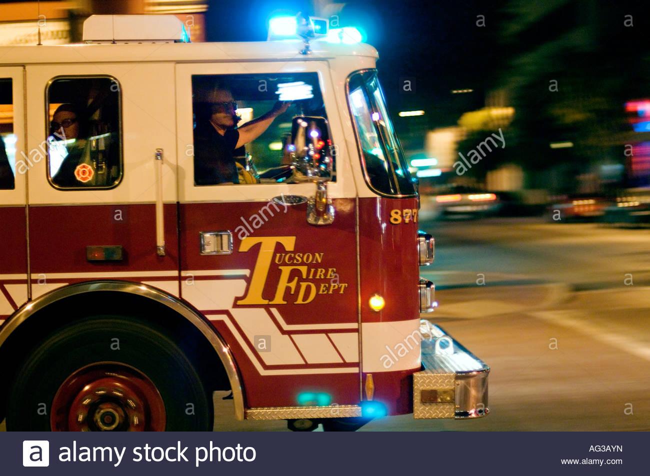 Fire truck responding to an emergency call entering traffic stock fire truck responding to an emergency call entering traffic intersection in downtown tucson arizona at night freerunsca Choice Image