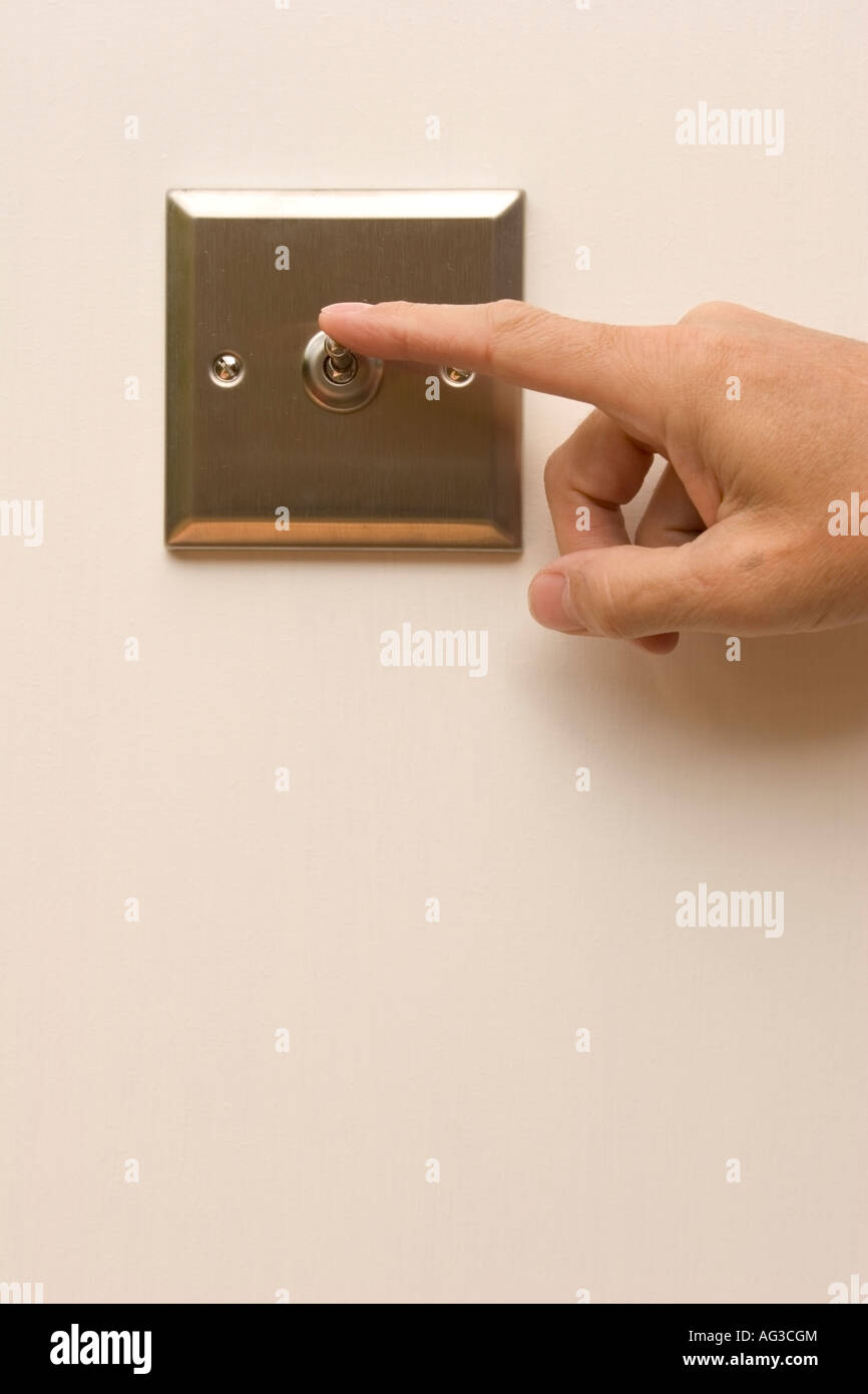 Male hand switching off a wall mounted light switch - Stock Image