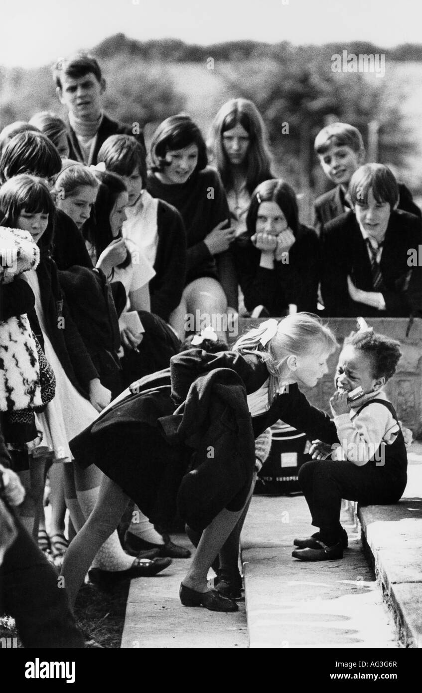 Vintage 1969 bw print Maltby S. Yorks secondary school pupils crowd round a little black girl who has fallen and - Stock Image