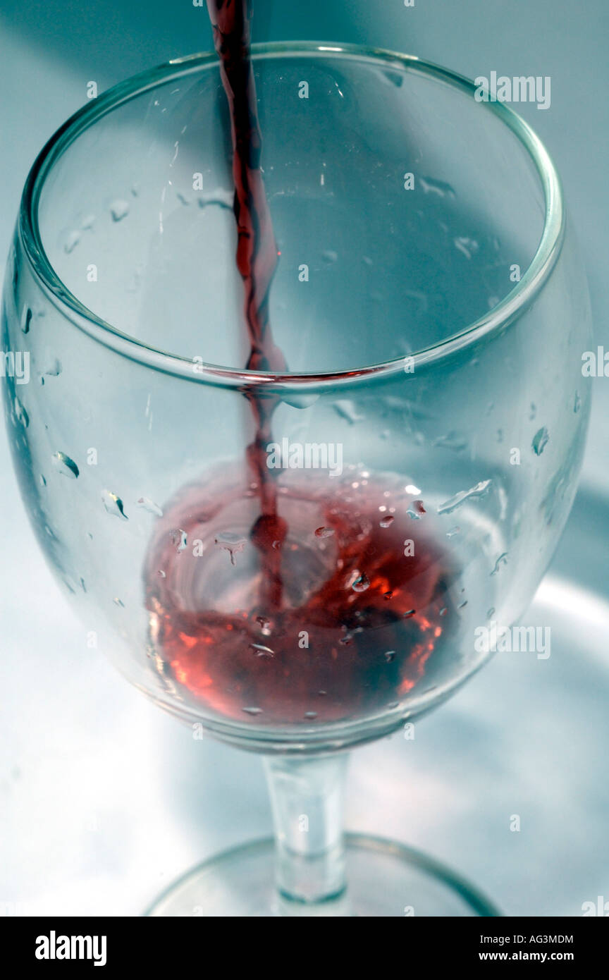 Red wine flowing into wine glass - Stock Image