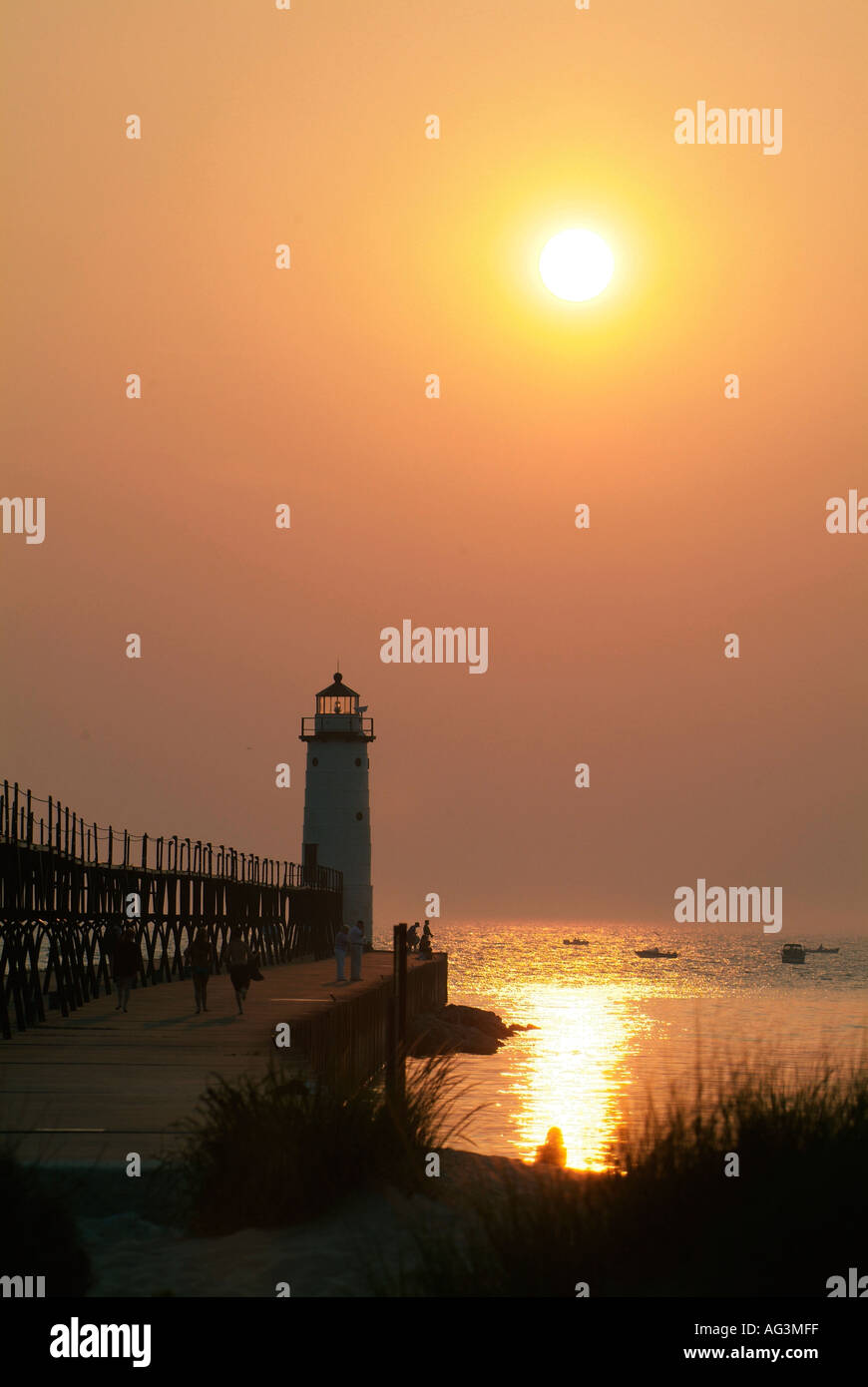 Sunset behind the lighthouse on Lake Michigan at Manistee Michigan beach bhz - Stock Image