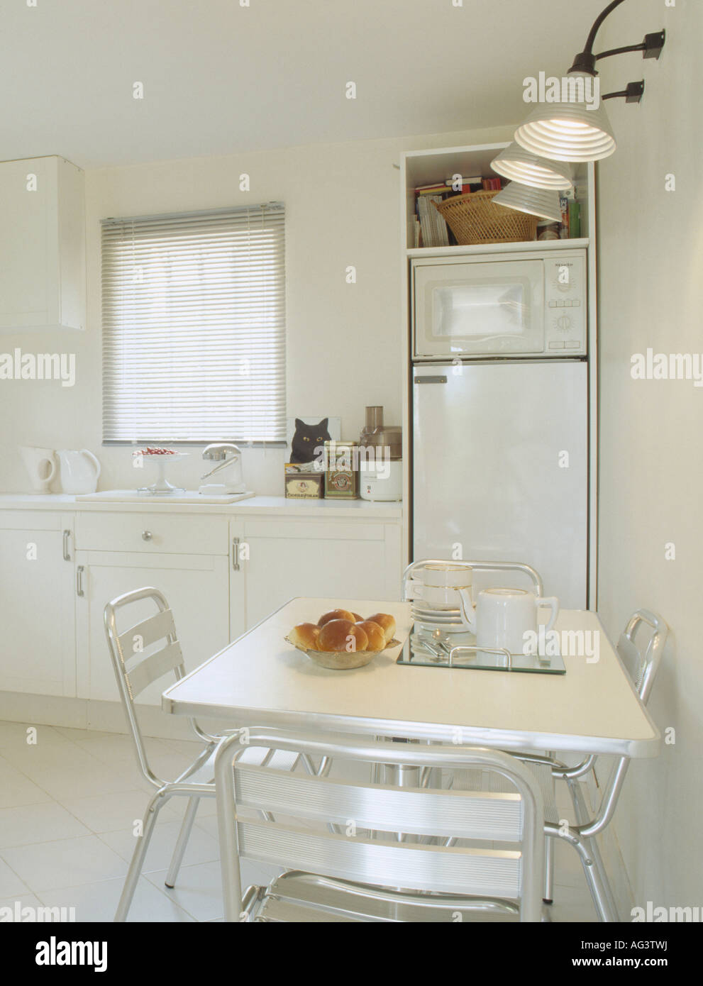 Metal Lights Above Metal Chairs And Table In Modern White Kitchen Stock Photo Alamy