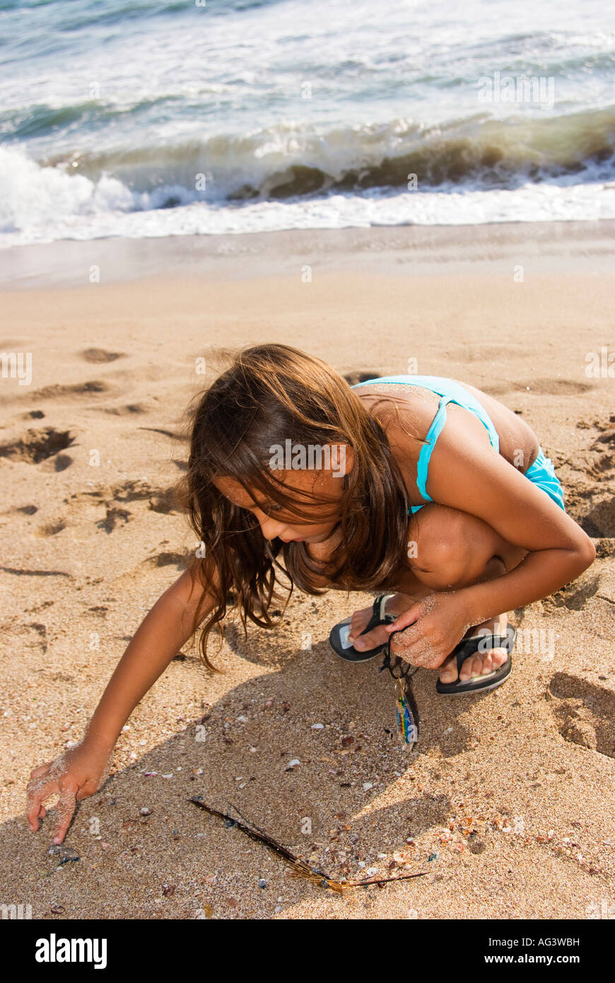 young mexican girl on a summer beach trip crouched playing in sand by Pacific ocean shoreline - Stock Image