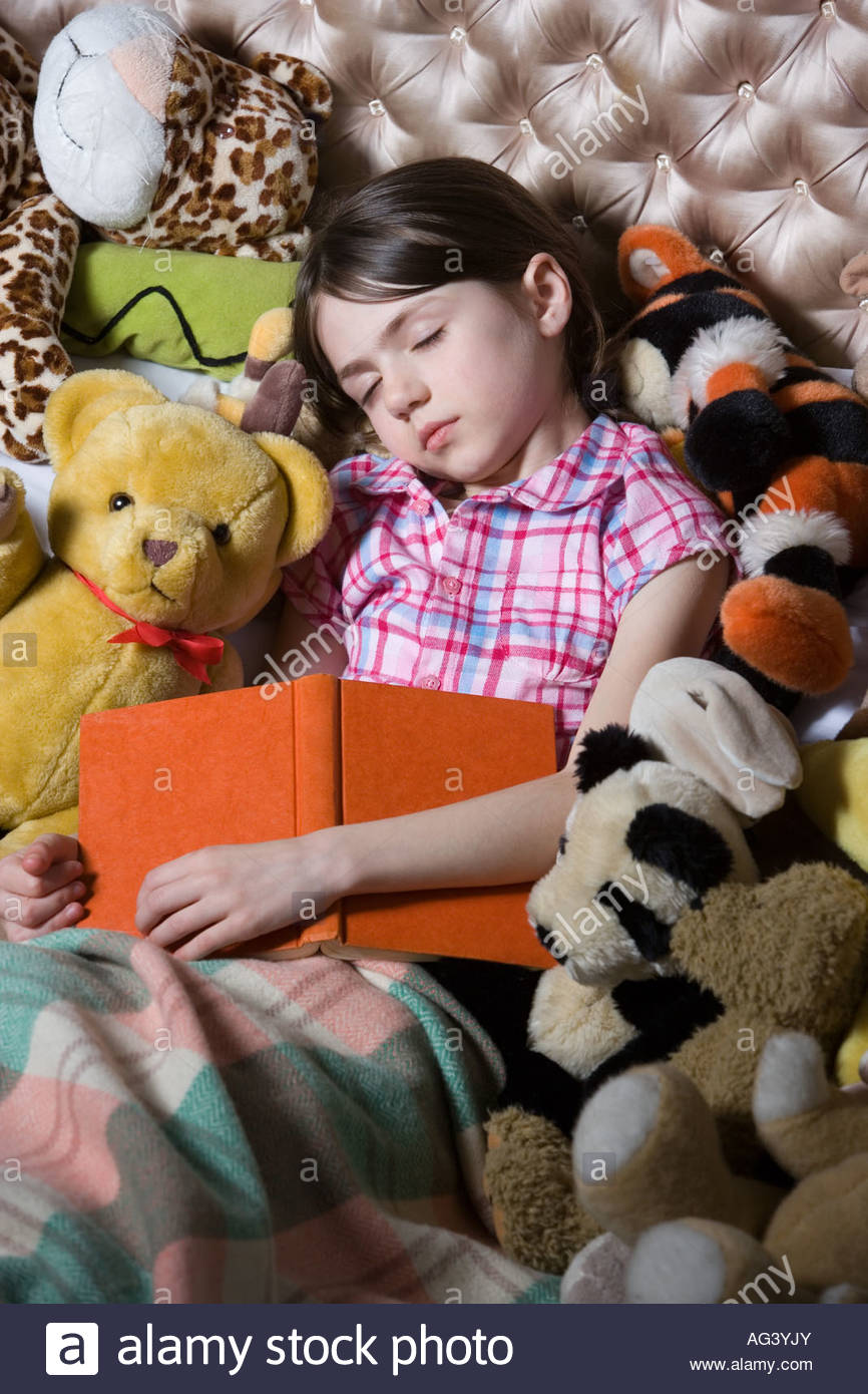 Sleeping girl with book and toys - Stock Image