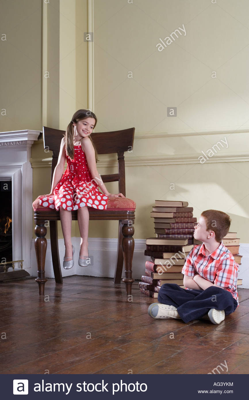 Girl on chair and boy on floor - Stock Image