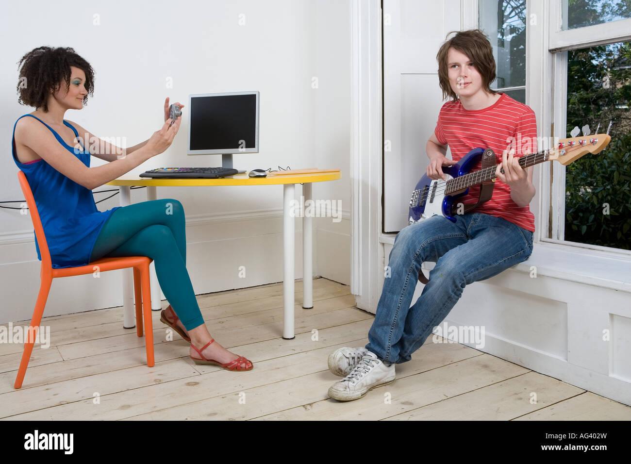 Girl photographing boy playing guitar - Stock Image