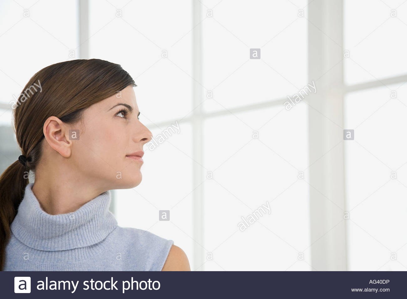 Woman looking at window - Stock Image
