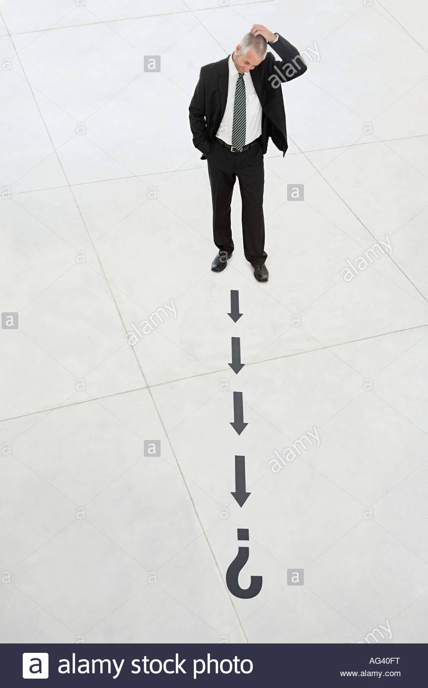 Businessman looking at arrows and question mark - Stock Image