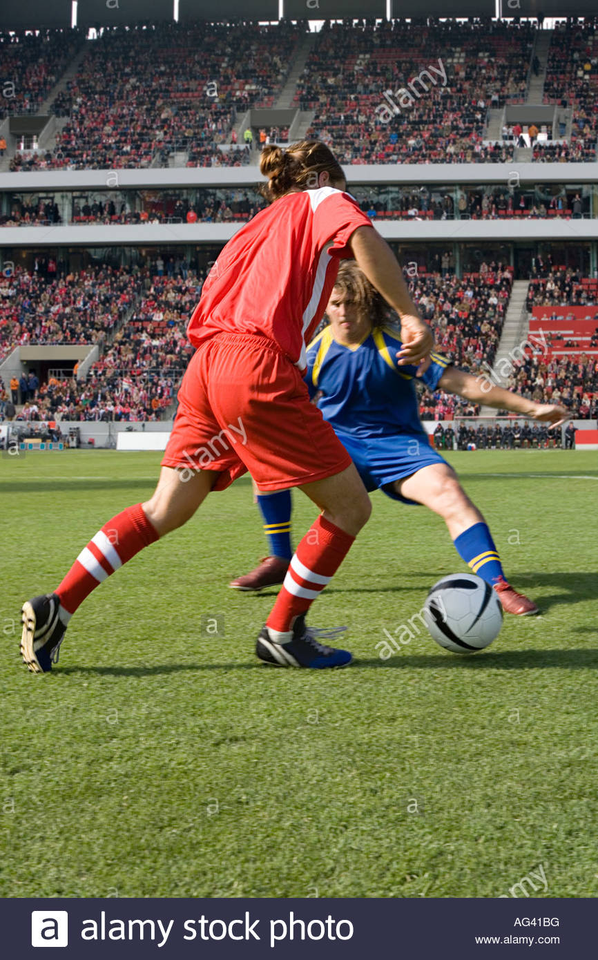 Opposite player tackling footballer - Stock Image