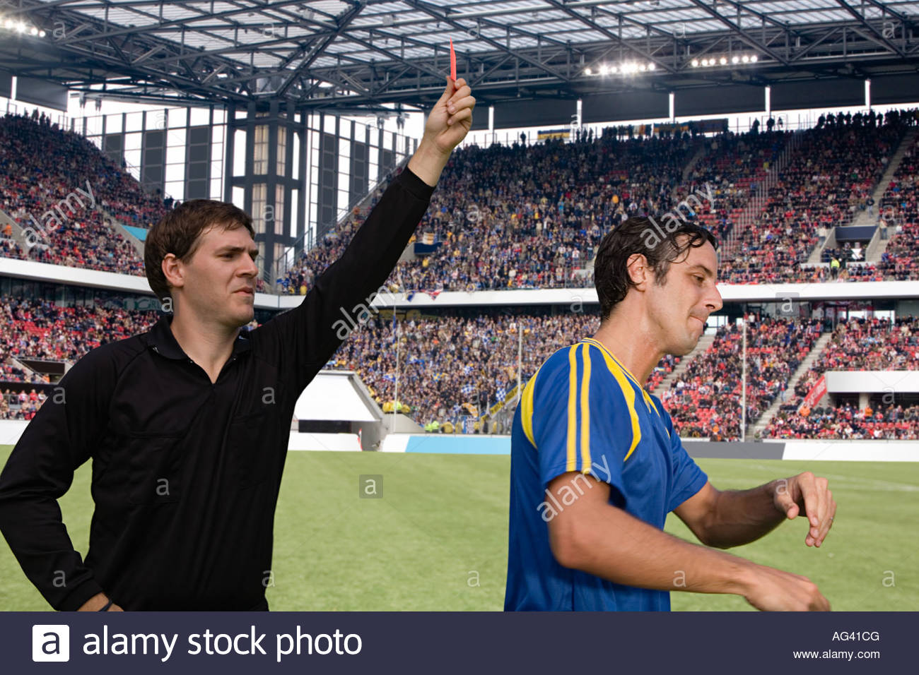 Referee giving a footballer a red card - Stock Image