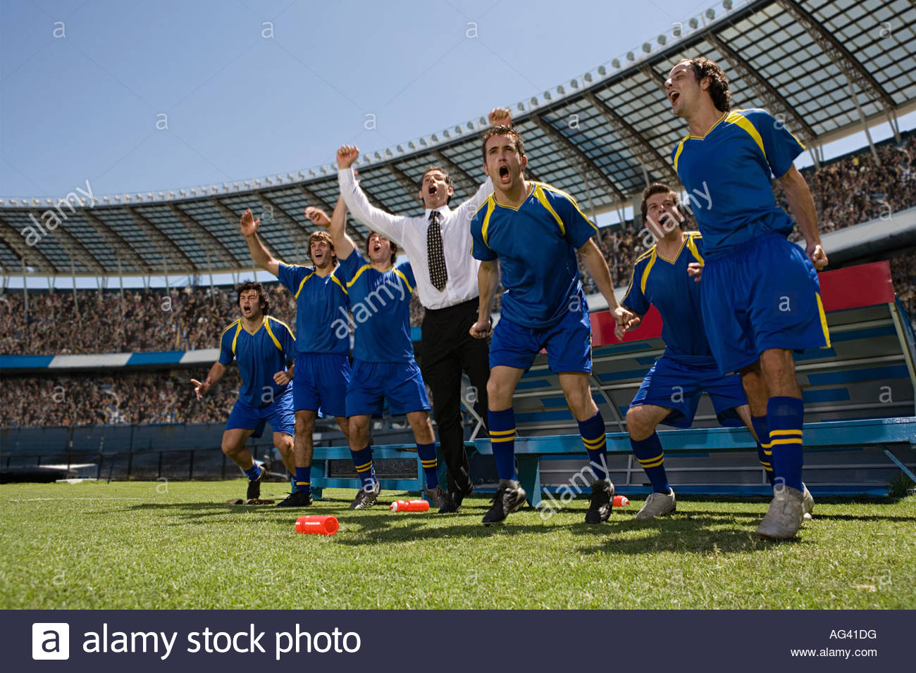 Football manager and footballers celebrating - Stock Image