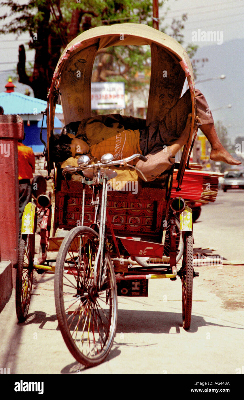 A tricycle driver takes a nap in his vehicle in the streets of Kathmandu nepal - Stock Image