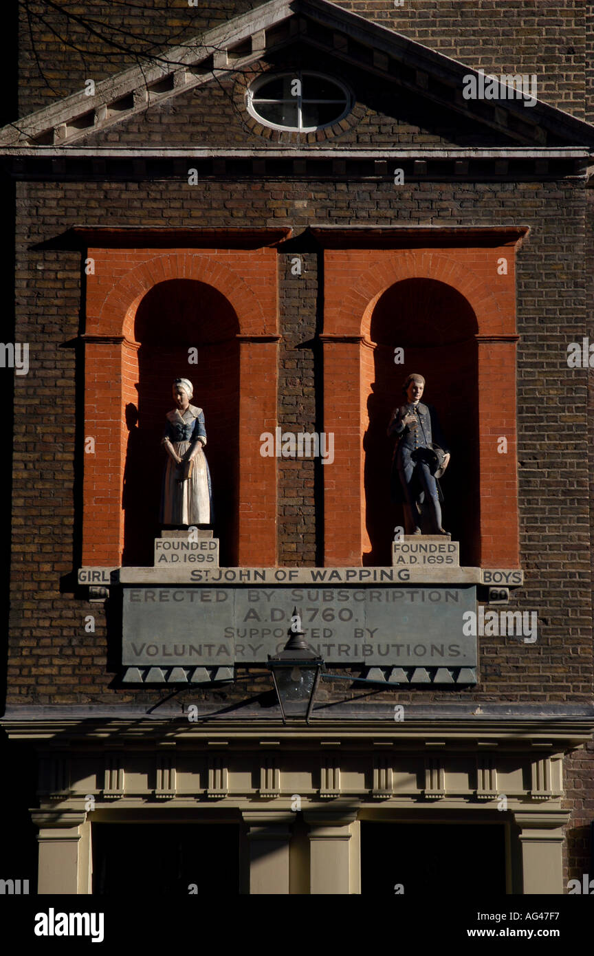 ST JOHN SCHHOL OLD 1695 FOUNDED EDUCATION STATUES REFORM BOY GIRL WAPPING - Stock Image