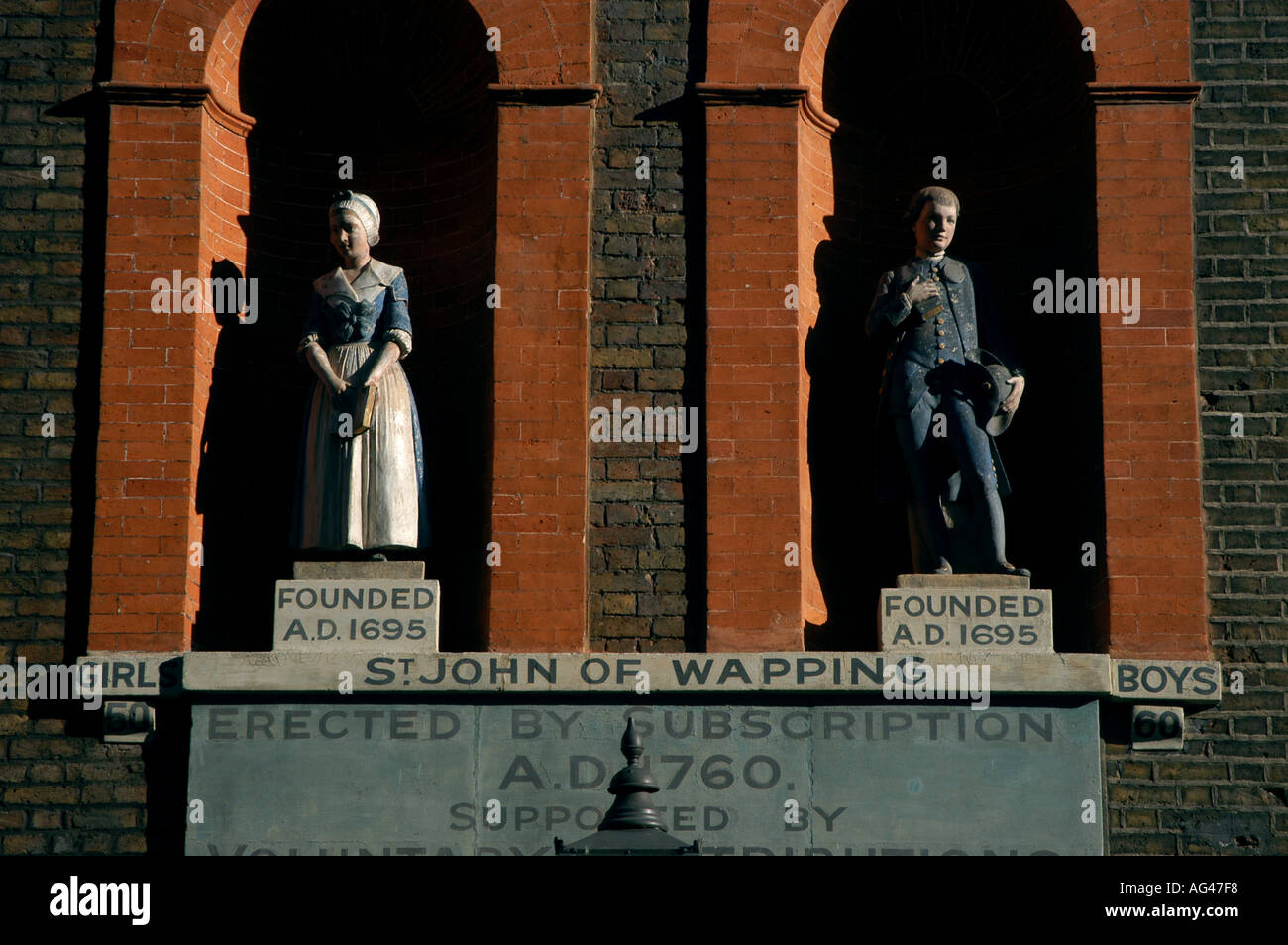 LONDON HISTORY ST JOHN SCHHOL OLD 1695 FOUNDED EDUCATION STATUES REFORM BOY GIRL WAPPING - Stock Image