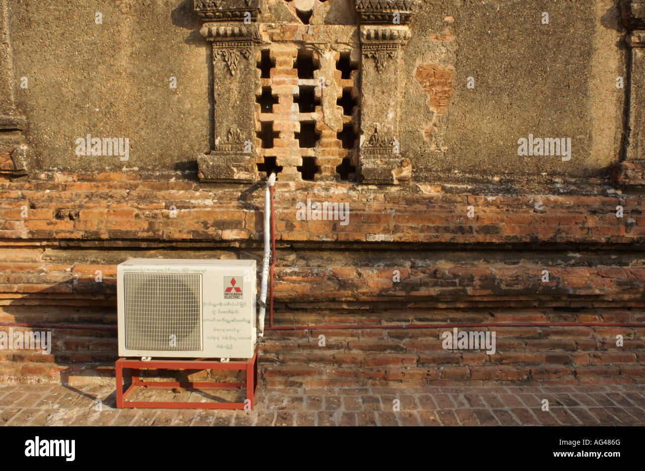 A modern air conditioning unit set up to cool a 900 year old temple in Myanmar. - Stock Image