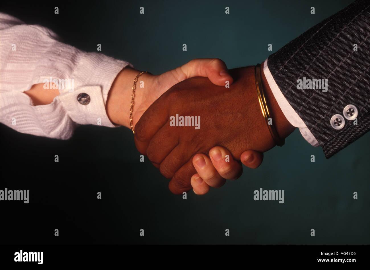 Handshake betwwn white female and black man 1795 Stock Photo