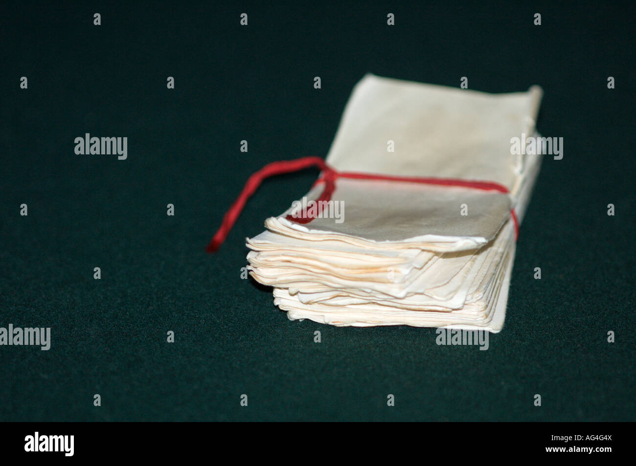 White Ballots on Green Felt Background Tied with a Red Cord - Stock Image