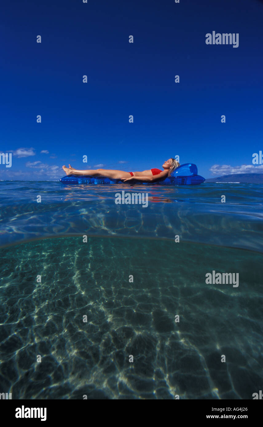 An above and below view of girl floating on a blue mat in Lahaina Maui Stock Photo