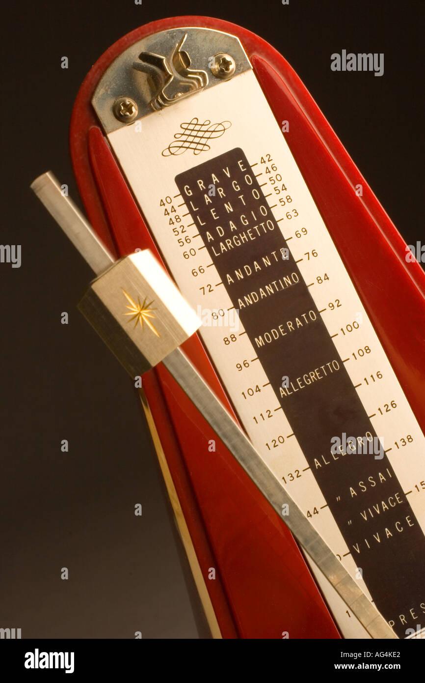Red metronome with swinging pendulum - Stock Image